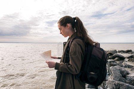 Photo pour Vue latérale du jeune routard avec la queue tenant la carte contre du paysage marin sous le ciel couvert - image libre de droit