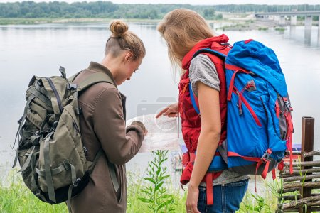 Two female travelers looking down at map at river