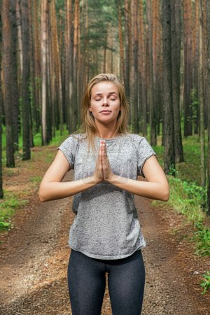 blonde girl with eyes closed with hands in namaste in forest