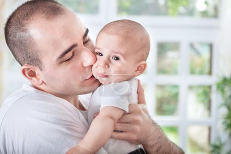 Gentle young father comforting crying baby