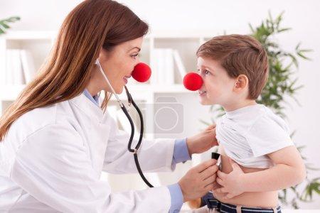 Souriant adorable femme médecin clown écouter patient coeur