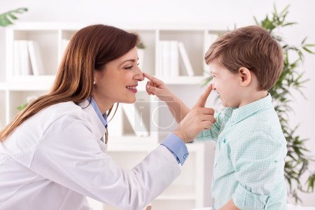 Photo pour Young doctor and child enjoy and playing together touching noses - image libre de droit