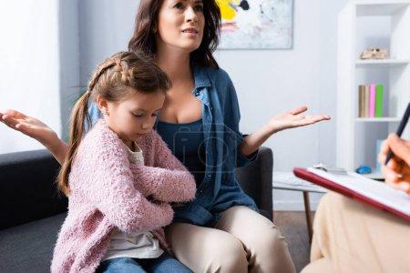 Photo pour Mère inquiète apportant fille avec les bras croisés au psychologue - image libre de droit