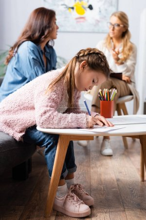 Photo for Little girl patient drawing picture while visiting psychologist with mother - Royalty Free Image