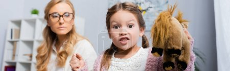 Photo for Angry little girl patient with toy and clenched fist visiting psychologist, banner - Royalty Free Image