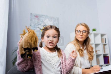 Photo for Angry little girl with toy and clenched fist visiting psychologist - Royalty Free Image