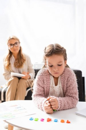 Photo for Girl patient calculating with figures while visiting psychologist - Royalty Free Image