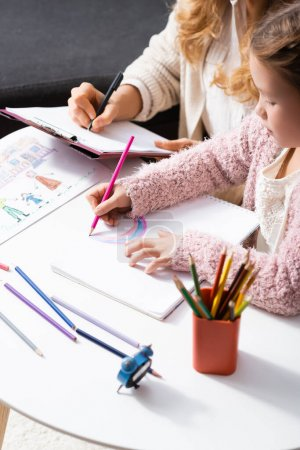 Photo for Little girl drawing pictures with colorful pencils while visiting psychologist - Royalty Free Image