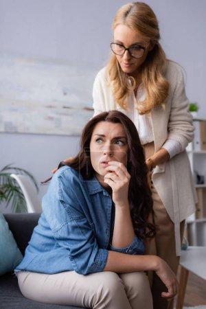 blonde woman therapist in eyeglasses calming patient