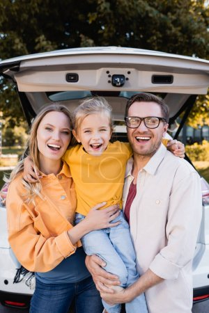 Photo for Cheerful girl hugging parents near car during travel outdoors - Royalty Free Image