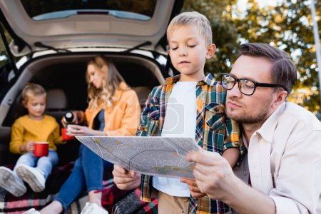 Father and son looking at map near mother with girl and car on blurred background