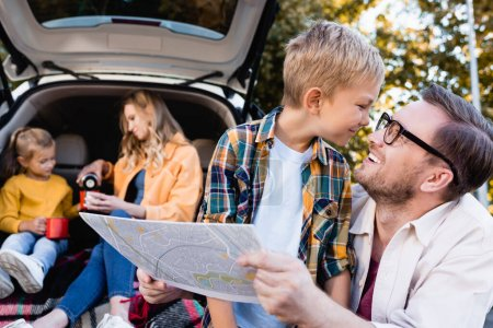 Smiling man holding map near son and wife with daughter near car on blurred background