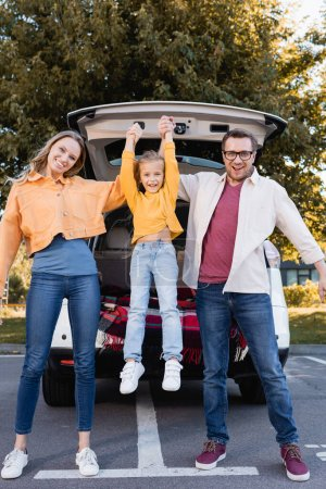 Photo for Cheerful parents holding daughter near car outdoors - Royalty Free Image