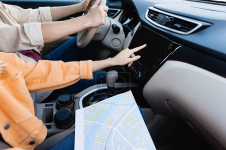 Vue recadrée de la femme avec carte à l'aide d'un système audio pendant que le mari conduit la voiture