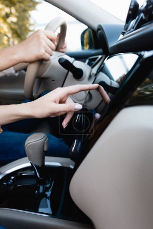 Cropped view of woman using audio system while husband driving auto
