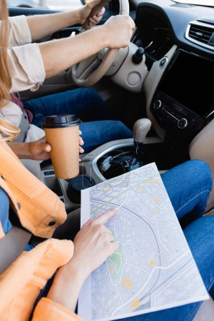 Cropped view of woman with coffee to go pointing at map while husband driving car