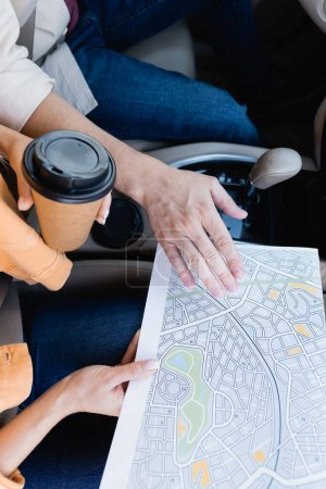 Cropped view of woman holding map and coffee to go near husband in car