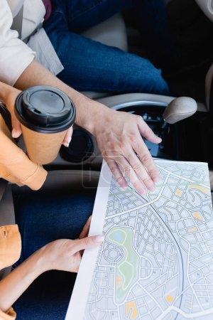 Ausgeschnittene Ansicht einer Frau, die Karte und Kaffee in der Hand hält, um ihrem Mann im Auto nahe zu kommen