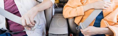 Photo pour Vue recadrée des parents tenant des ceintures de sécurité près de l'enfant sur fond flou dans la voiture, bannière - image libre de droit