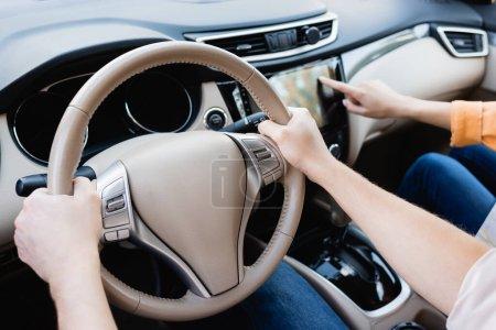 Zugeschnittene Ansicht des Mannes Auto fahren, während Frau mit Audio-System auf verschwommenem Hintergrund
