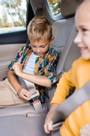 Child locking safety belt near smiling sister on blurred foreground in car