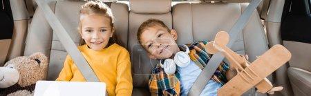 Photo pour Enfants souriants avec tablette numérique et jouets assis en auto, bannière - image libre de droit