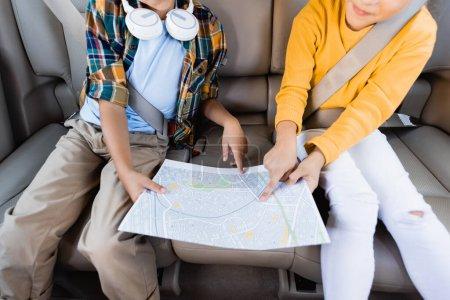 Vue recadrée de la fille pointant avec le doigt sur la carte près du frère avec des écouteurs dans la voiture