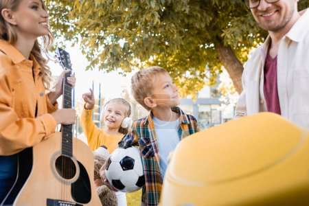 Photo for Cheerful kids with football and soft toy standing near parents with suitcase and acoustic guitar on blurred foreground - Royalty Free Image