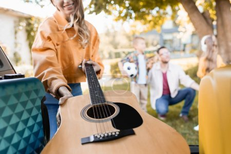 Cropped view of smiling woman taking acoustic guitar from car trunk near family on blurred background outdoors