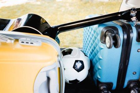 Photo pour Football, valises et guitare acoustique dans le coffre de voiture - image libre de droit