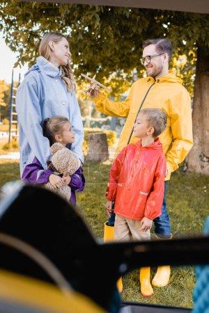Photo pour Famille souriante tenant des jouets près de la voiture pendant les vacances d'automne - image libre de droit