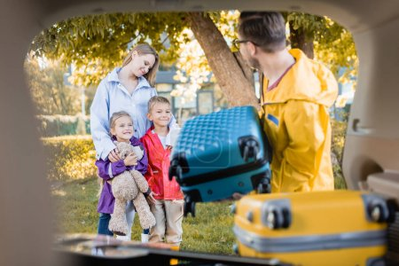 Smiling woman hugging kids near husband holding suitcase and trunk of car on blurred foreground