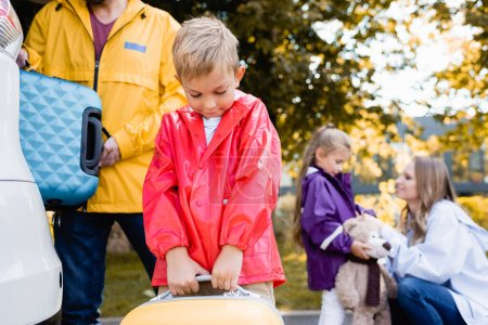 Photo for Boy holding suitcase near car and family on blurred background outdoors - Royalty Free Image