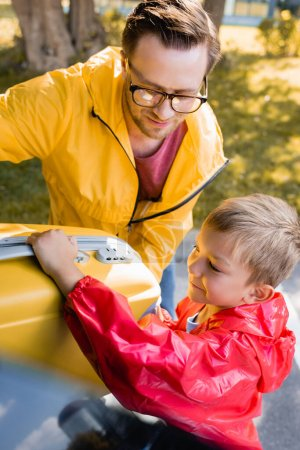 Photo for Smiling kid holding suitcase near father and trunk of car outdoors - Royalty Free Image