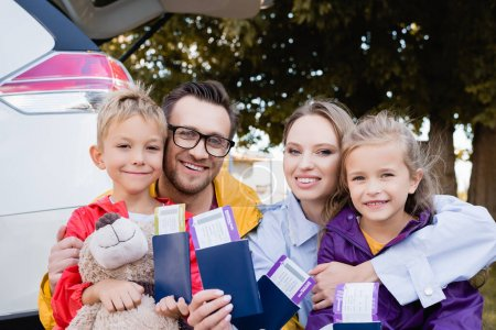 Photo for Cheerful family holding passports and air tickets near auto outdoors - Royalty Free Image