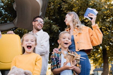 Photo for Cheerful kids with toys standing near parents holding passports and suitcase beside car outdoors - Royalty Free Image