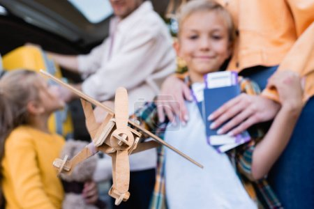 Toy plane in hand of boy near family with passports and car on blurred background