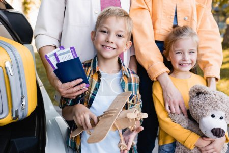 Photo for Smiling kids with toys standing near parents with passports and suitcase in car outdoors - Royalty Free Image