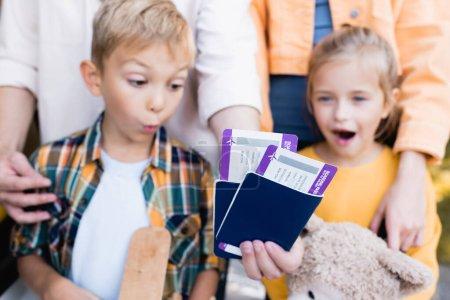 Photo pour Passeports avec billets d'avion en main de l'homme près des enfants excités sur fond flou - image libre de droit