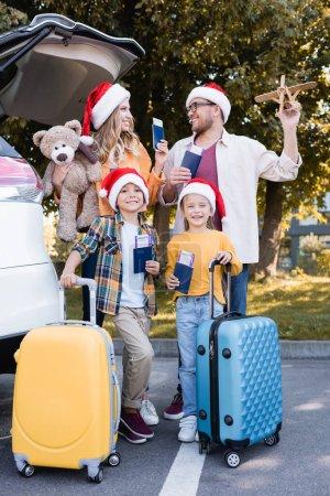 Photo pour Famille souriante dans des chapeaux de Père Noël tenant des documents avec des billets d'avion près des valises et de l'auto à l'extérieur - image libre de droit