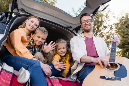 Man holding acoustic guitar near kids waving hands and smiling wife in trunk of car