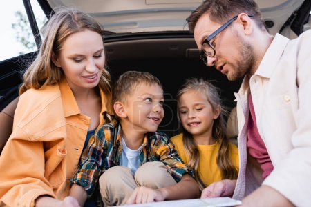 Photo for Cheerful family looking at map on blurred foreground near car trunk - Royalty Free Image