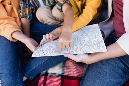 Cropped view of kid pointing at map near parents on blanket