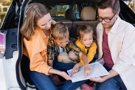Smiling kids pointing with fingers at map near parents in car trunk