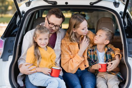 Photo for Cheerful kids holding cups near parents in trunk of auto - Royalty Free Image