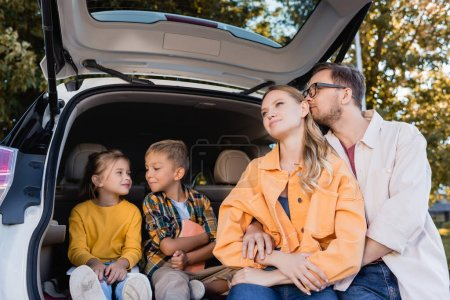 Photo for Man hugging wife near smiling kids in trunk of car - Royalty Free Image