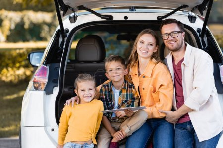 Cheerful family with map looking at camera near trunk of car outdoors