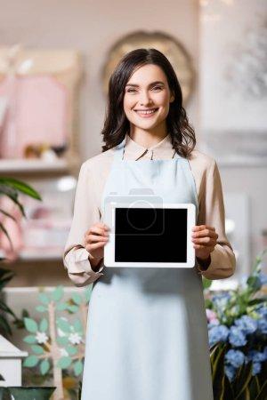 Photo pour Fleuriste souriant regardant la caméra tout en tenant tablette numérique avec écran blanc sur fond flou - image libre de droit