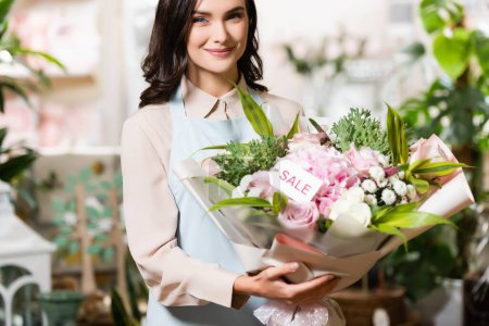 happy florist holding bouquet with sale lettering on tag while looking at camera near blurred plants on background