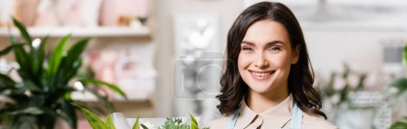 happy florist looking at camera in flower shop on blurred background, banner